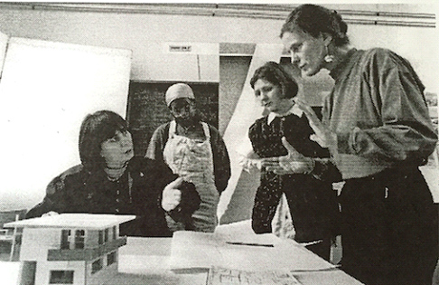 4 women sit and stand around a table discussing a student project.